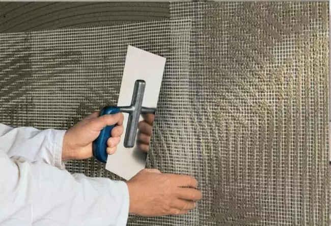 до облицовки фасада плиткой укладывают специальную сетку, которая удерживает раствор от растрескивания