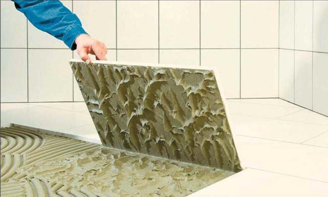 проверка качества укладки путем подъема одной уложенной плитки на клей