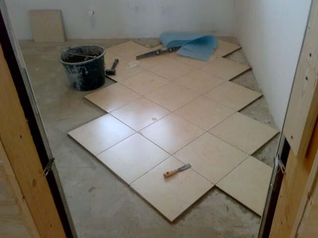процесс укладки плитки от стены