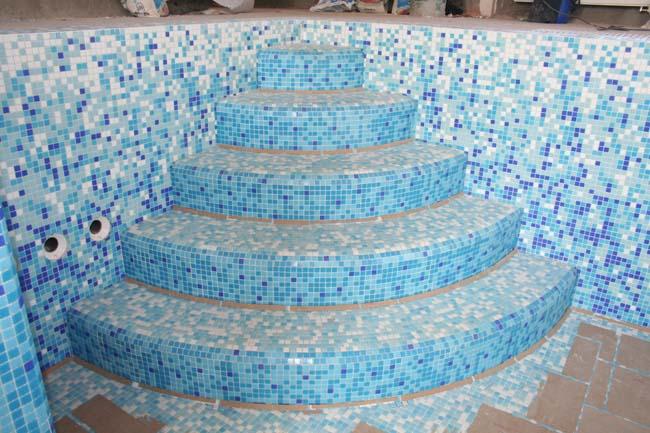 голубая мозаика красиво обрамляет ступени в бассейн