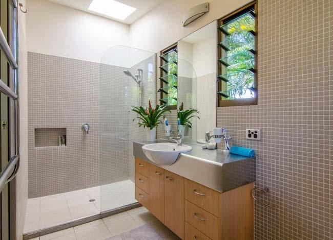 Стеклянная кабинка в сочетании с мозаичной кладкой визуально увеличивает пространство душевой