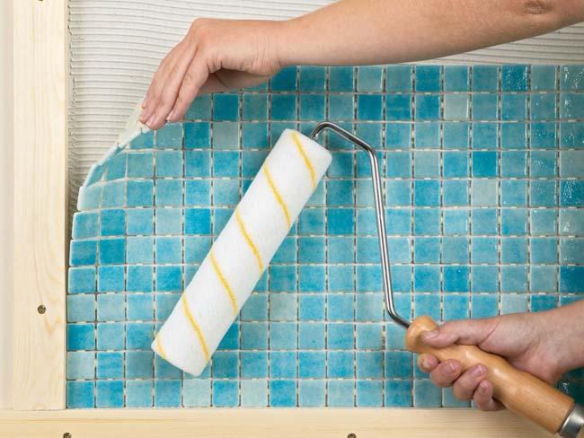 процесс укладки мозаичной плитки на стену