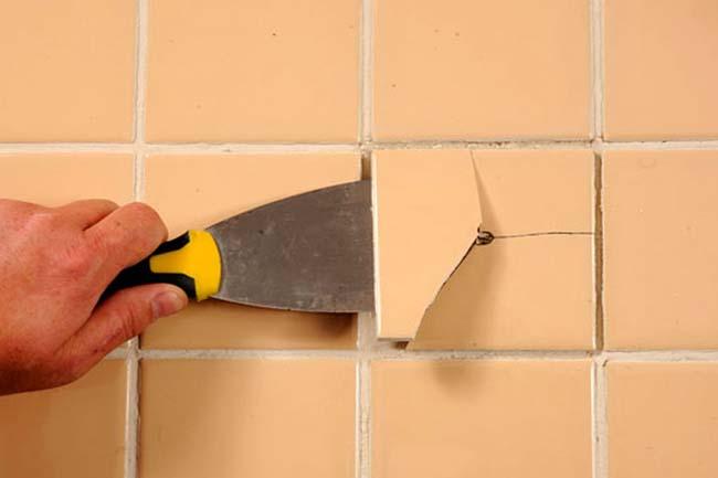 шпателем аккуратно снимаем треснувшую плитку со стены