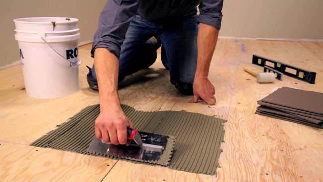 наносим специальный клей для укладки плитки на деревянный основания