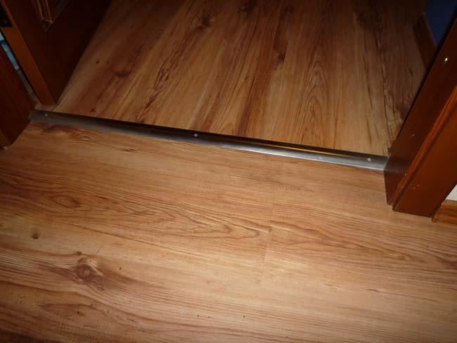 металлический порожек закрывает стык плитки и плитки