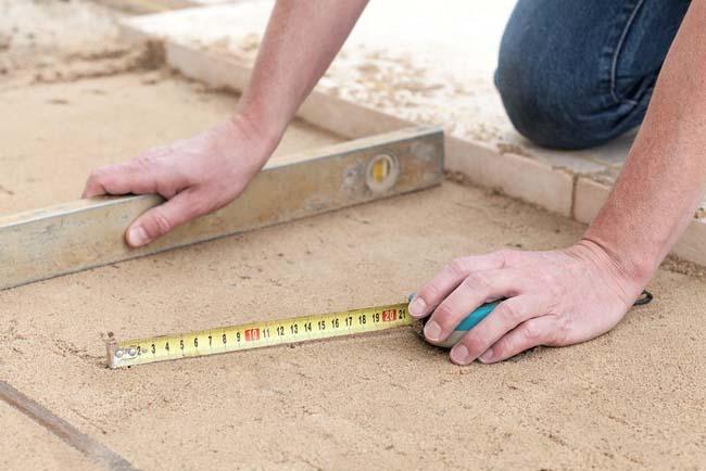 слой песка уплотняем и выравниваем для последующей укладки на него тротуарной плитки