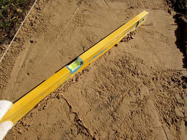 проверяем уровнем правильность укладки песочного слоя